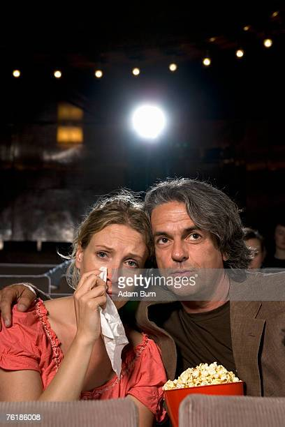 a woman crying whilst sitting with a man in a movie theater - romance film stock photos and pictures