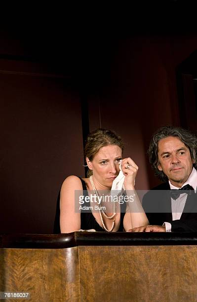 A woman crying whilst sitting with a man in a theater box