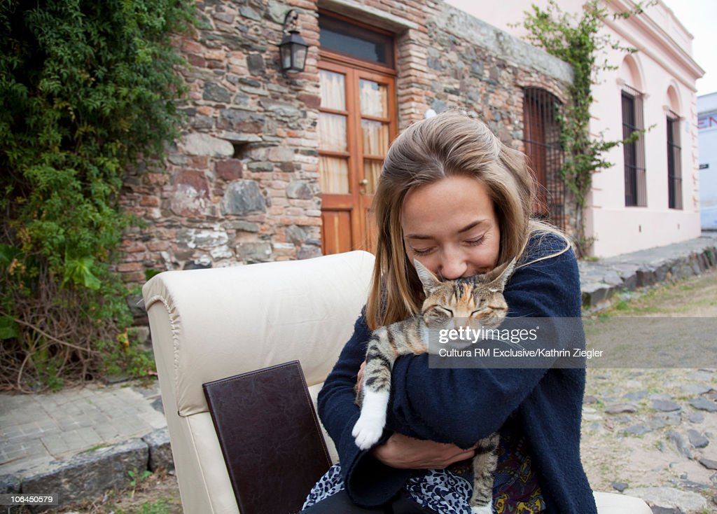 Woman cuddling cat : Bildbanksbilder