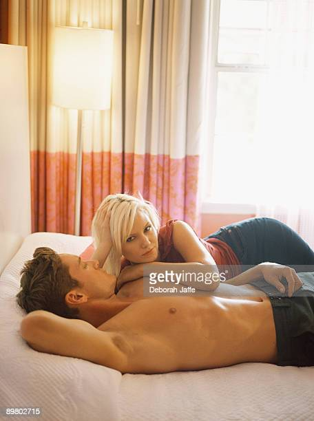 Woman cuddling up to man in bed
