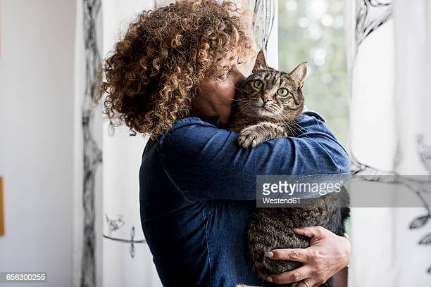 Woman cuddling with cat by the window