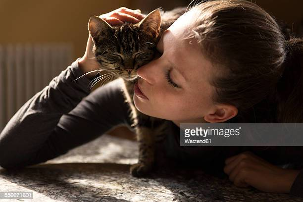 Woman cuddling with cat