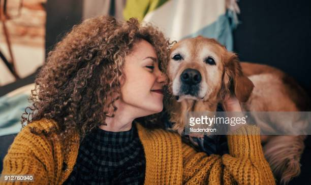 woman cuddling with her dog - golden retriever stock pictures, royalty-free photos & images