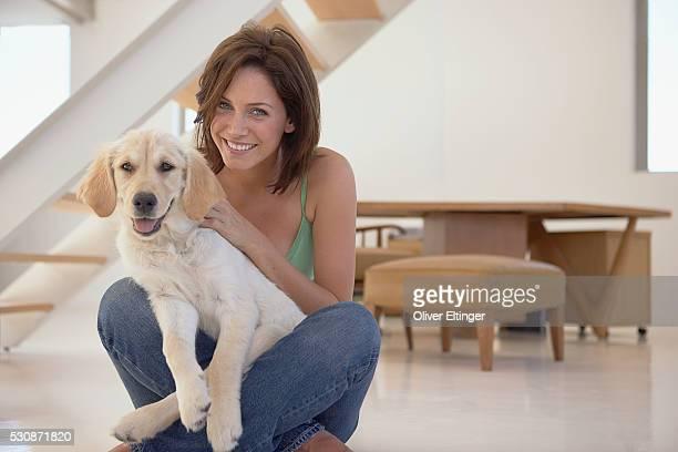 woman cuddling with puppy - oliver eltinger stock-fotos und bilder