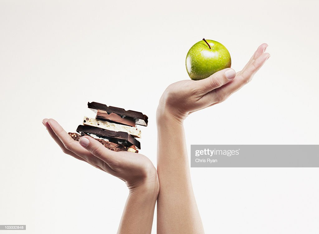 Woman cupping green apple above chocolate bars : Stock Photo