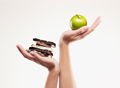 Woman cupping green apple above chocolate bars - gettyimageskorea