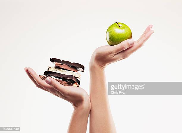 woman cupping green apple above chocolate bars - apple fruit stock photos and pictures