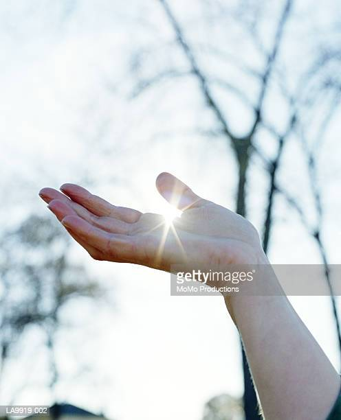 Woman cupping hand, sunlight shining through fingers