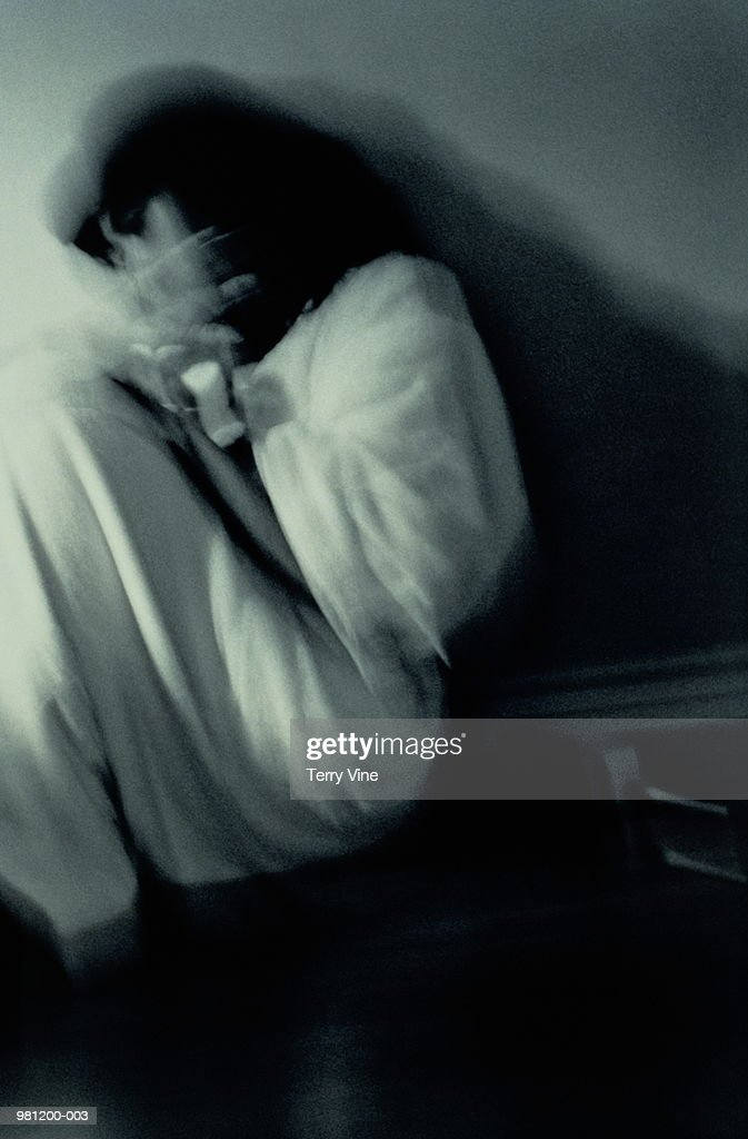Woman curled on floor shielding herself with hands, blurred (B&W) : Stock Photo