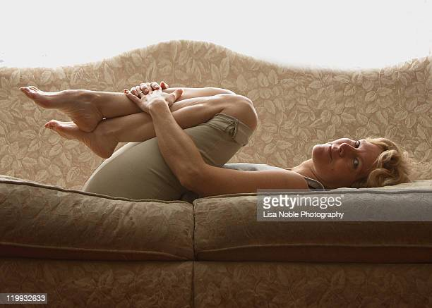 Woman curled up on sofa holding legs