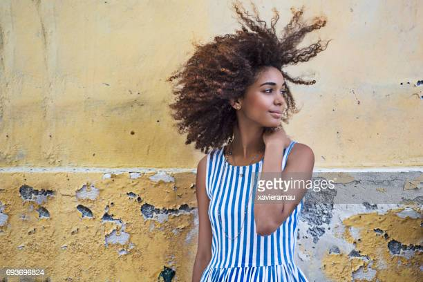 Woman curly hair looking away over weathered wall