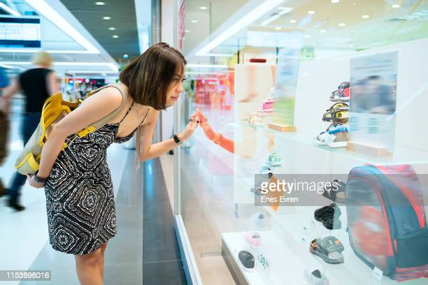 Woman customer looking at shop store retail display in mall