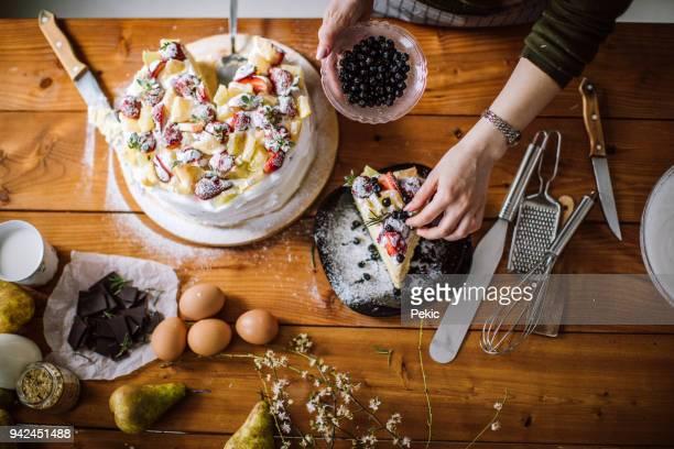 Frau Schnitt einen Stück Kuchen für den Geburtstag Zelebranten