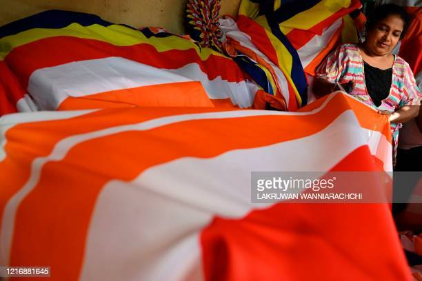 A woman cuts a fabric for a Buddhist flag in a shop ahead of Poson festival in Colombo on June 2 2020 Sri Lankan Buddhists are preparing to celebrate...