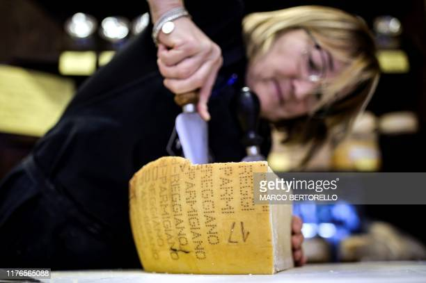 A woman cuts a piece of Parmigiano Reggiano Parmesan cheese on October 18 2019 in a cheese shop in Saluzzo near Turin With Washington starting to...