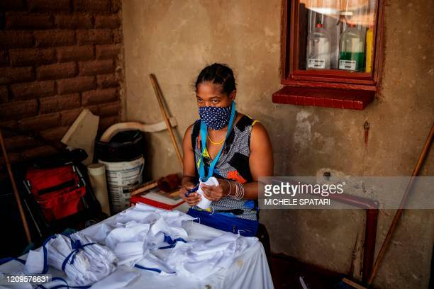 Woman cuts cotton fabric into pieces used to manufacture reusable face masks in Johannesburg's Alexandra township, on April 8, 2020. - Alexandra...