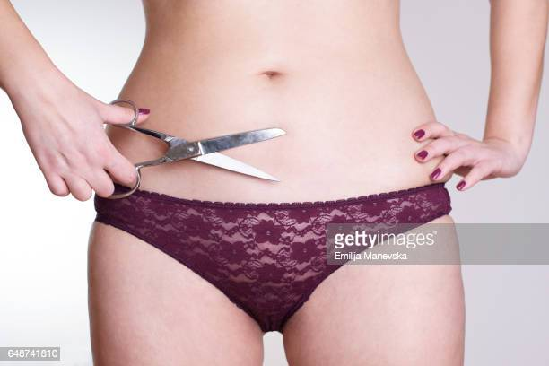 Woman cuts her belly by scissors. Weight loss concept