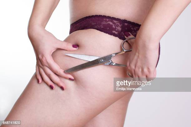 Woman cuts her buttocks by scissors. Weight loss concept