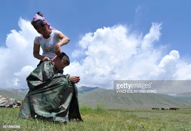 A woman cuts her son's hair outdoor at the SuuSamyr plateau500 meters above the sea level near the ancient Silk Road network of trade routes between...