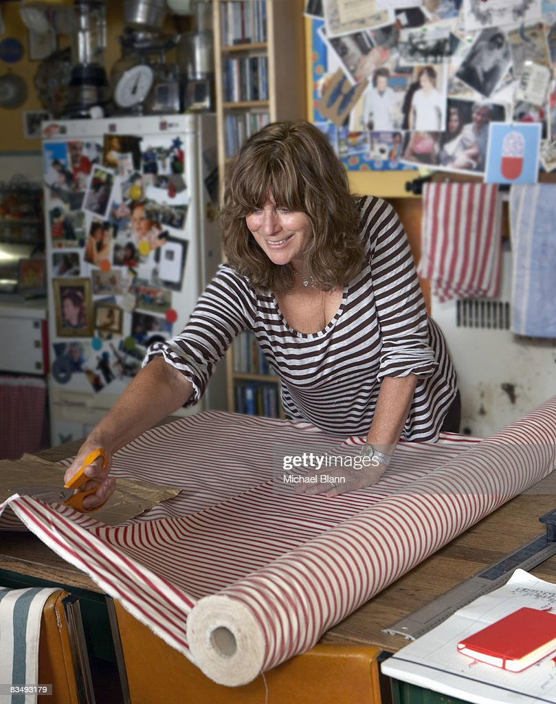 woman cuts material with scissors : Stock Photo