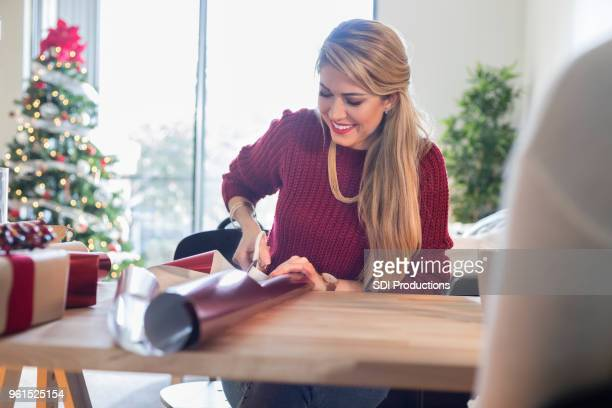 woman cuts rolled christmas wrapping paper at home - avvolto foto e immagini stock