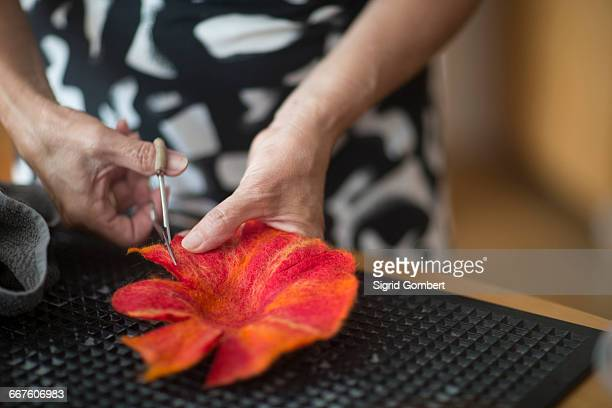 Woman cutting and shaping felt flower