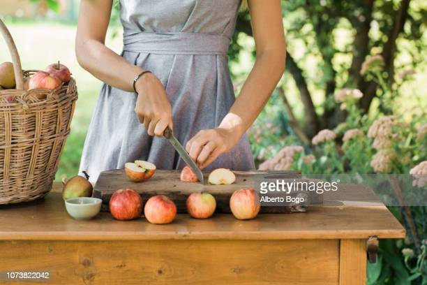 woman cutting apples on table - 果樹園 ストックフォトと画像