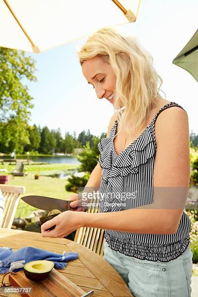 Woman cutting avocado, lake in background