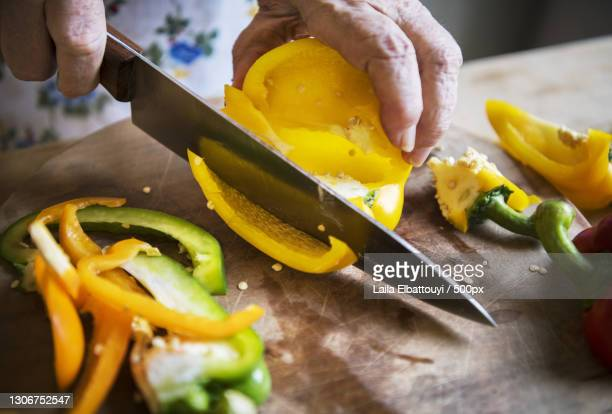 woman cutting bell pepper on a cutting board,united states,usa - bell pepper stock pictures, royalty-free photos & images