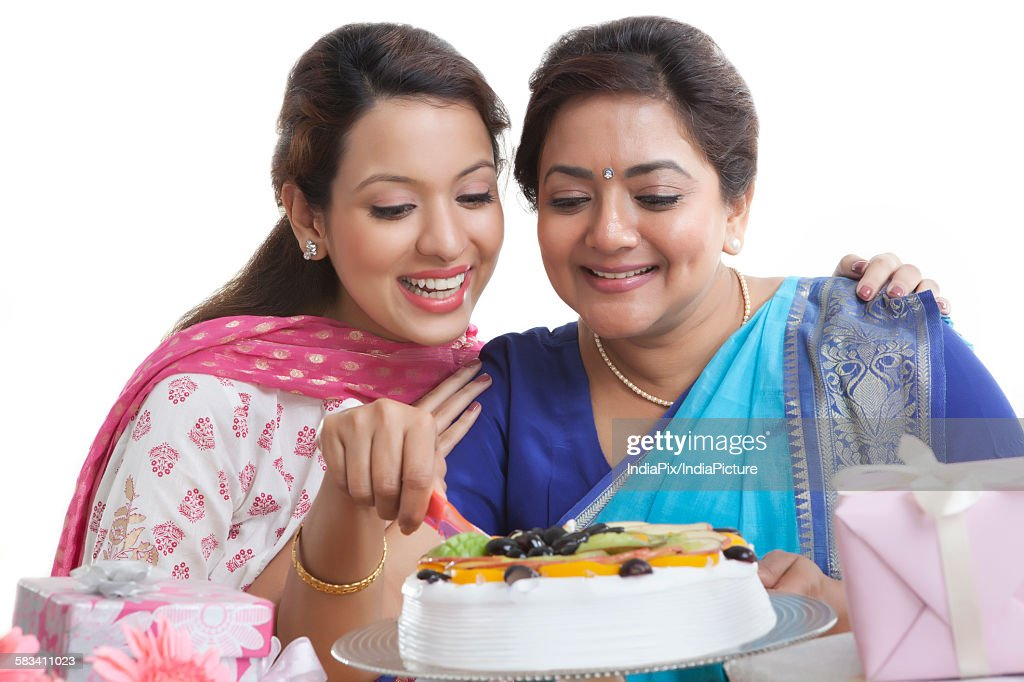Woman cutting birthday cake while daughter looks on : Stock Photo