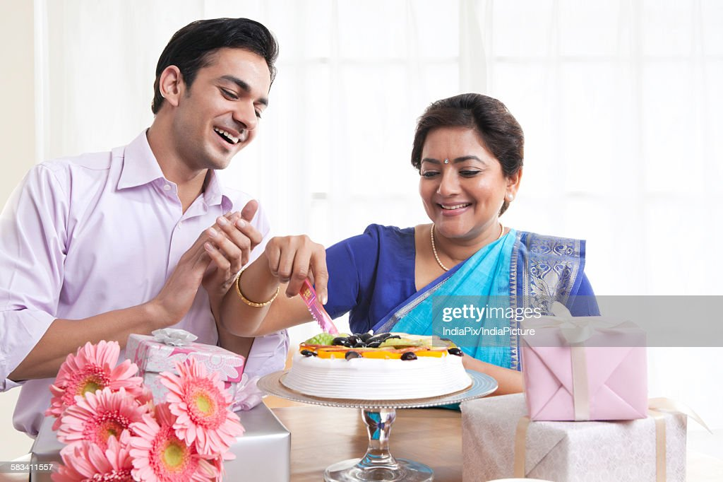 Woman cutting birthday cake while son looks on : Stock Photo