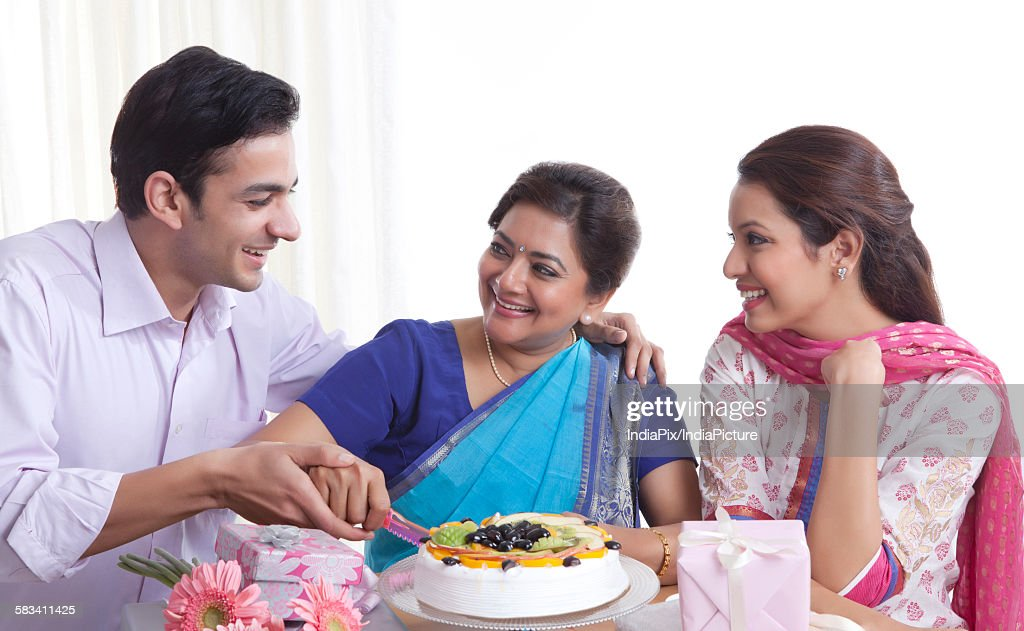 Woman cutting birthday cake with a knife : Stock Photo