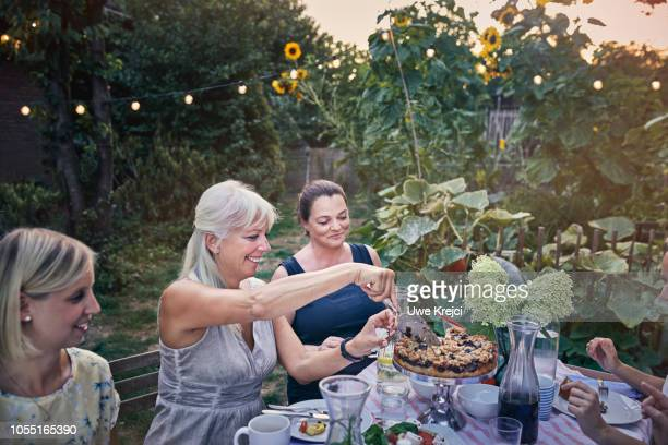Woman cutting cake at garden party