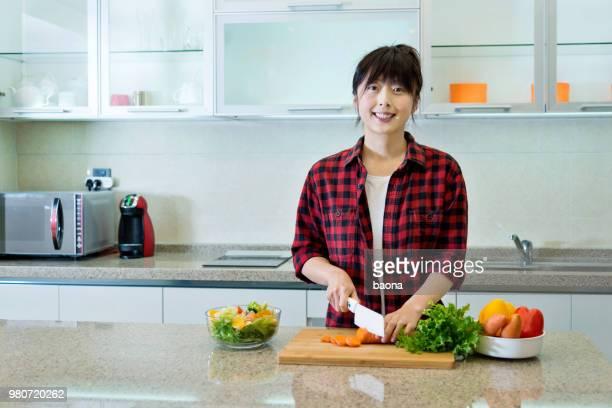 キッチン ボード上女性切断ニンジン - 根菜 ストックフォトと画像