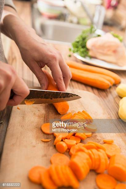 Woman cutting carrots on cutting board in kitchen, Munich, Bavaria, Germany