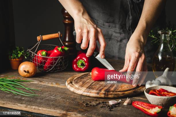 woman cutting chili peppers to prepare red pepper soup - chopping food stock pictures, royalty-free photos & images