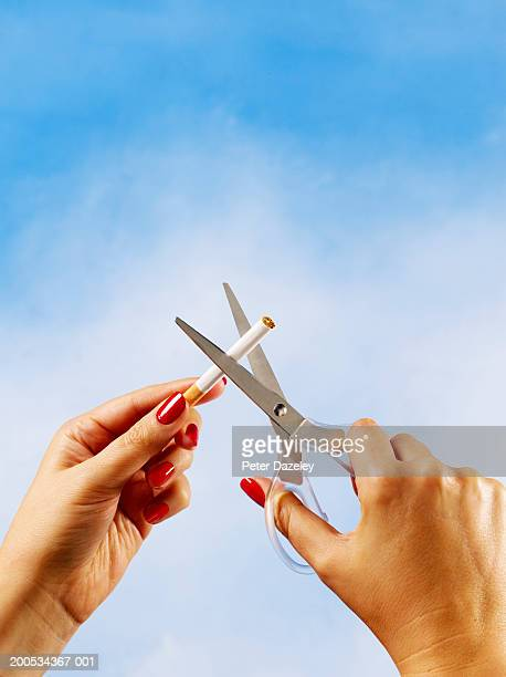 Woman cutting cigarette with scissors, close-up of hands