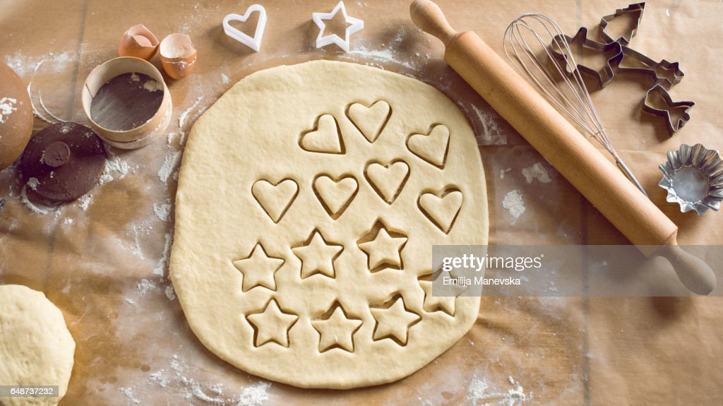 Woman cutting cookie dough in kitchen : Stock Photo