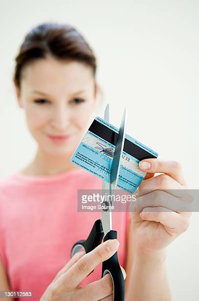 Woman cutting credit card with pair of scissors
