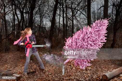Woman Cutting Down Pink Christmas Tree Stock Photo | Getty Images