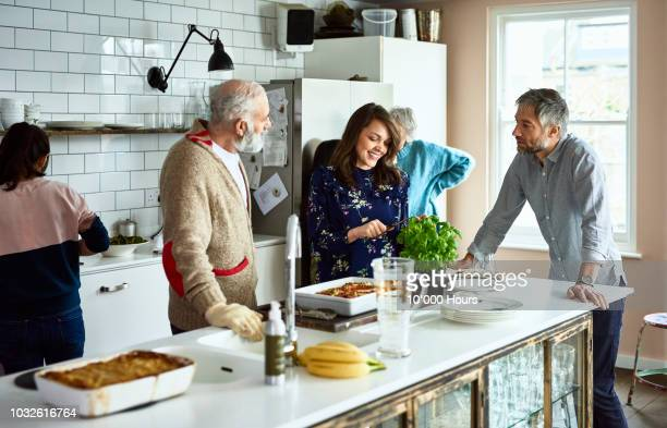 woman cutting fresh basil with husband and father in law in family kitchen - in law relations stock pictures, royalty-free photos & images