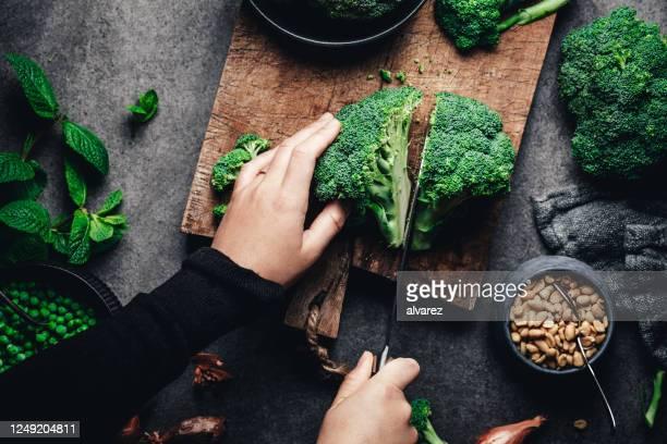 woman cutting fresh broccoli - cortando preparando comida imagens e fotografias de stock