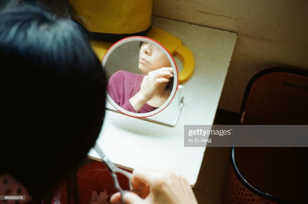 A woman cutting hair by her self with scissors and a mirror. : Stock-Foto