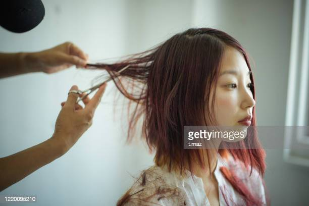 woman cutting hair dyed red - dyed red hair stock pictures, royalty-free photos & images
