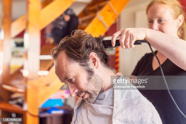 a woman cutting her husband's hair at home - cutting stock pictures, royalty-free photos & images