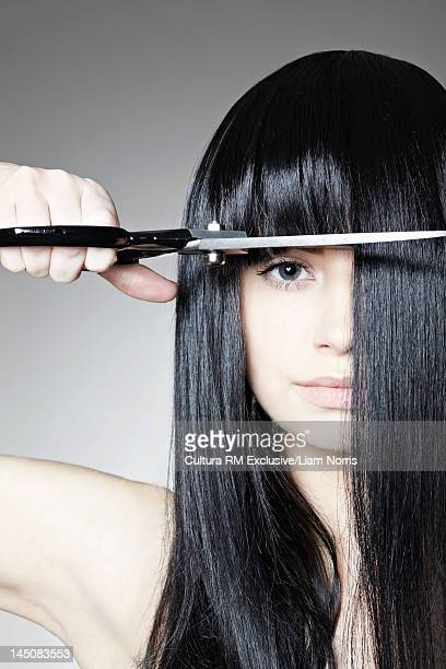 Woman cutting her own bangs