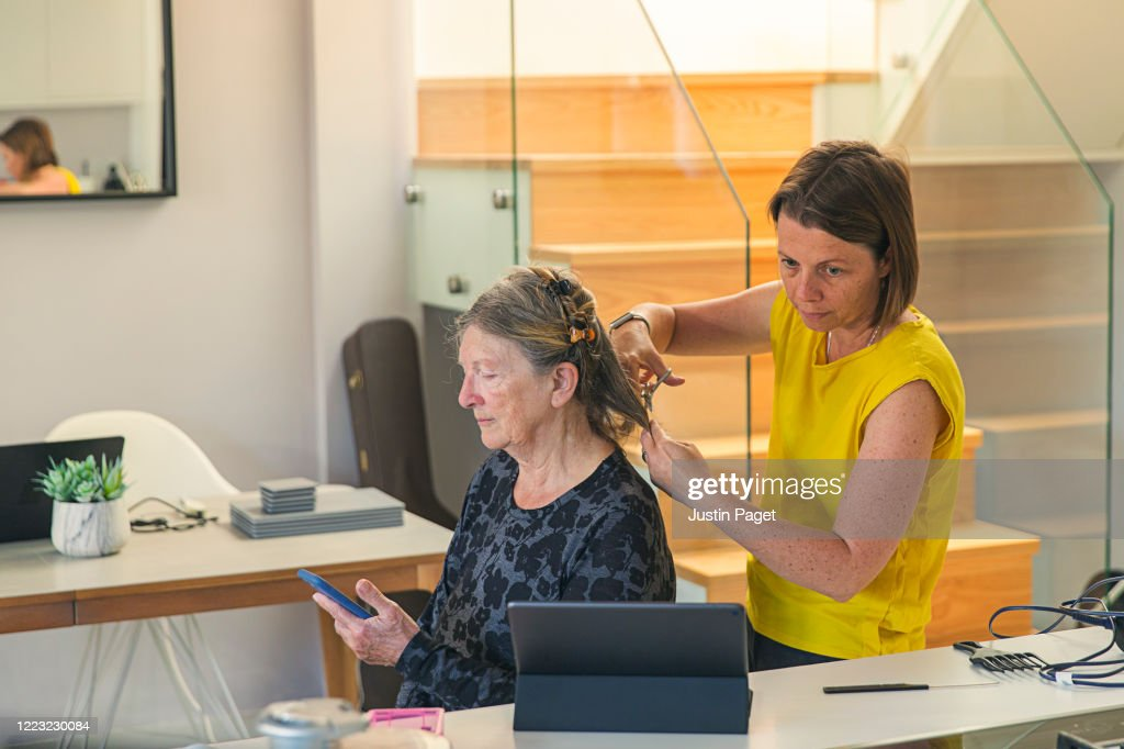 Woman cutting her senior mother's hair : Stock Photo