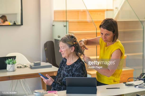 Woman cutting her senior mother's hair