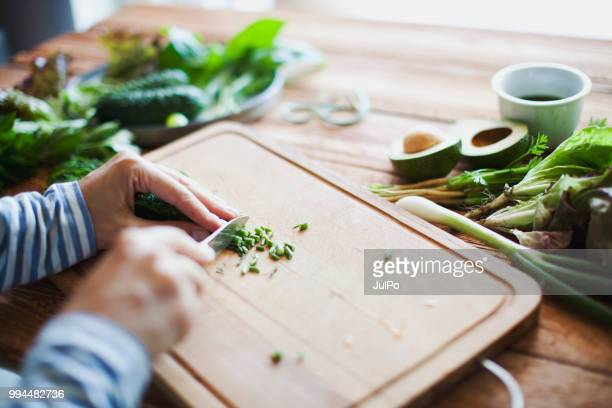 Woman cutting herbs and vegetables