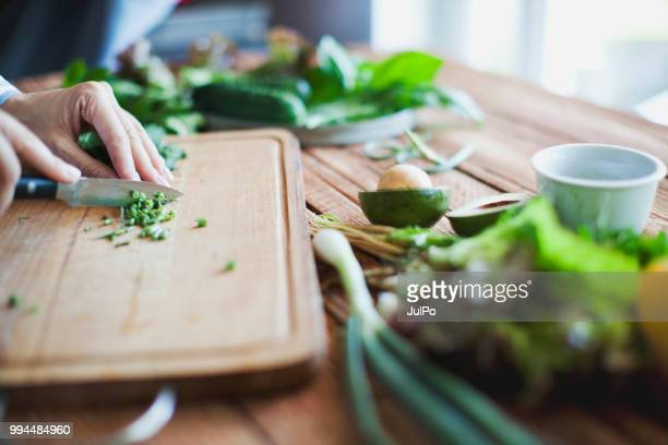woman cutting herbs and vegetables - cutting stock pictures, royalty-free photos & images